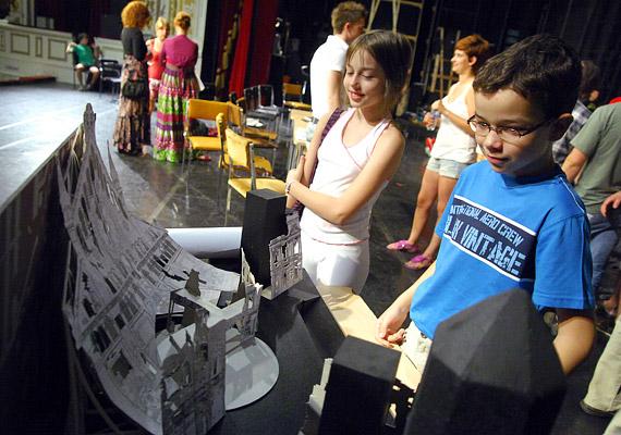 A gyerekek érdekődve figyelik a színpadi díszlet papírból készült tervét.