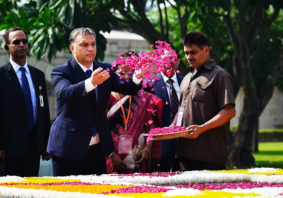 Orbán Viktor virágszirmokat szór Mahátma Gandhi emlékhelyén Újdelhiben.