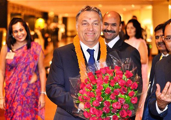Itt éppen Indiába érkezik, ahol hatalmas virágcsokorral fogadják a nagyon boldog magyar miniszterelnököt.