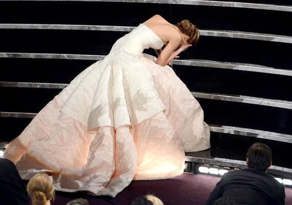 Mégsem ő volt az, aki elesett: Jennifer Lawrence a díjért igyekezett, amikor a földet söprő Dior haute couture ruhája kifogott rajta.