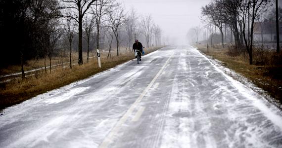 Egy férfi kerékpározik a behavazott úton Orosháza határában. Békés megyébe -12 Celsius-fokos hideg és orkán erejű szél kíséretében érkezett meg a havazás.