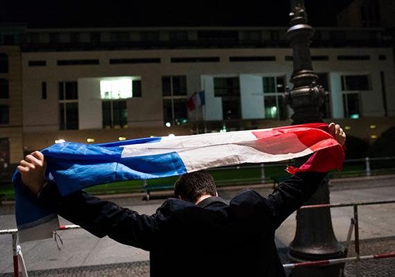 Egy francia zászlót tartó férfi áll Franciaország berlini nagykövetsége előtt 2015. november 14-én kora hajnalban.