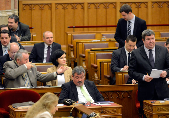 """A szocialista Gőgös Zoltán puskalövést imitált Tállai Miklós államtitkár felszólalása alatt a parlamentben. A Blikk felhívta a képviselőt, és megkérdezte, vajon hogy értette a gesztust, amire a politikus hihetetlen magyarázattal szolgált: """"Jót nevettem a képen, de nem akartam senkit lelőni. Tállai a Quaestor-ügyet az MSZP-re akarta kenni, mire én egy 2010. áprilisi határozatot mutogattam neki. Ebben az előző kormány alatt tiltották el a társaságot, hogy garantált befektetésként hirdesse a kötvényeit. Mivel influenzás vagyok, köhögni kezdtem, ledobtam a papírt, és a kezemet a számhoz tettem, miközben a fotós megörökítette a pillanatot"""" - idézi a lap a képviselőt."""