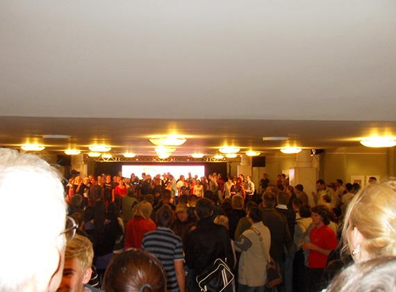 A színpadon összegyűlt tömeg éppen a rákkendroll lépéseit tanulgatja. Kérdés, hogy melyik szórakozóhelyen megy hasonló zene. Talán 1978 -Vár Klub...