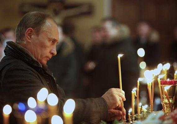 Az orosz ortodox vallású Putyin éppen egy gyertyát gyújt meg.