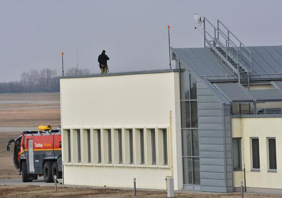 A Terrorelhárítási Központ egyik embere gépfegyverrel a kezében figyeli a repteret.