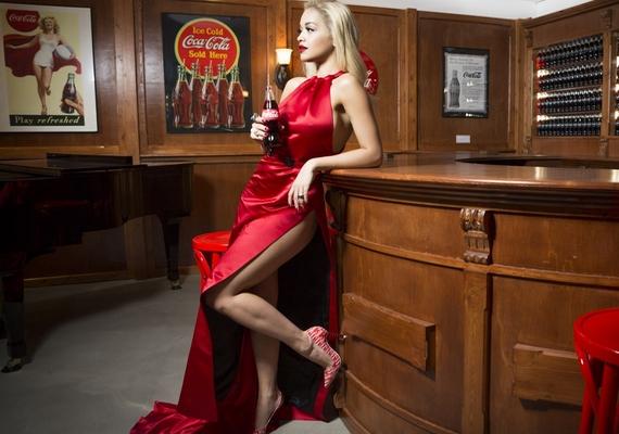 A róla készült reklámfotón egy magasan sliccelt, sötétebb piros estélyi ruhát viselt.