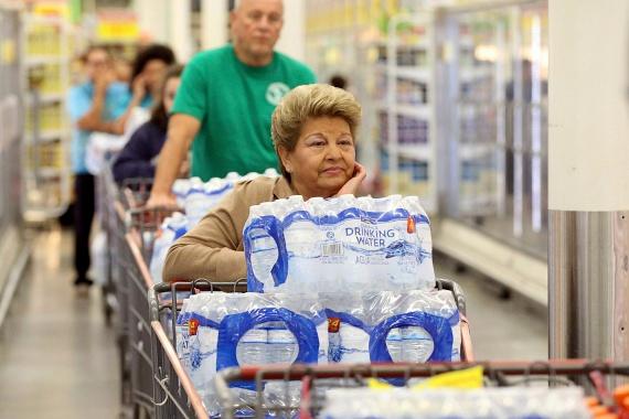 Kígyózó sorok a H-E-B áruházban: a vásárlók nagy mennyiségű palackozott vízzel felszerelkezve várják, hogy fizethessenek.