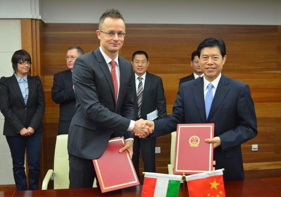 Nagy az öröm! Csung San kereskedelmi miniszterhelyettes kezet fog Szijjártóval, miután kétoldalú infrastrukturális keretmegállapodást írtak alá Pekingben november 13-án. Az egyezmény azt a stratégiai célkitűzést szolgálja, hogy Magyarország váljon a kínai áruk európai kivitelének közép-európai tranzitországává.