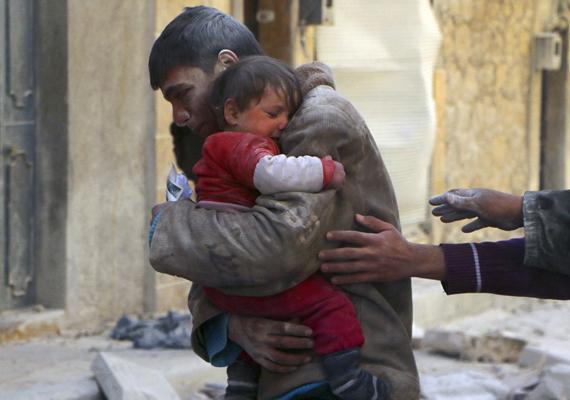 Gyermekét óvó apa a szíriai összecsapások közepette.