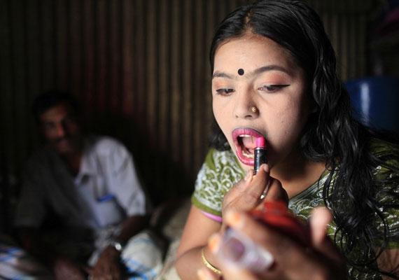 A 16 éves Maya rúzsozza magát egy kliense előtt.
