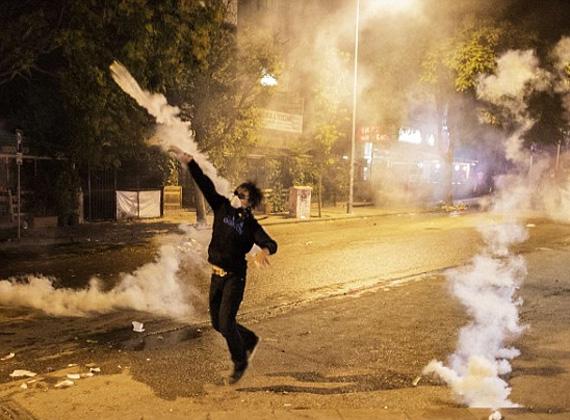 A rendőrök könnygázt is bevetnek a tüntetőkkel szemben, a képen egy fiatal férfi éppen visszadobja azt a rendőrök felé, a barikádon túlra.