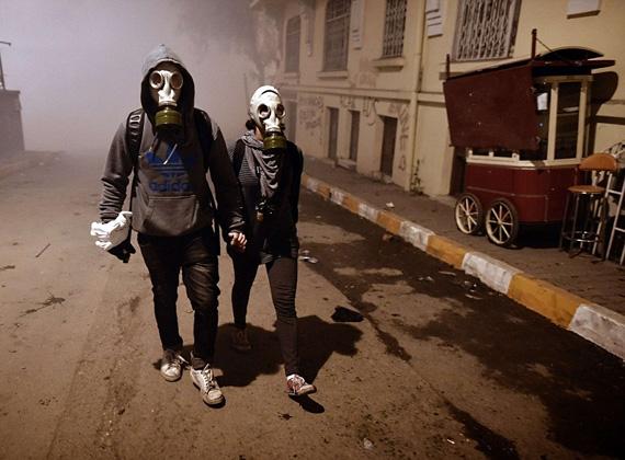 Gázálarcos pár sétál Isztambul utcáján, a háttérben a könnygáz okozta füstfelhőt látjuk.