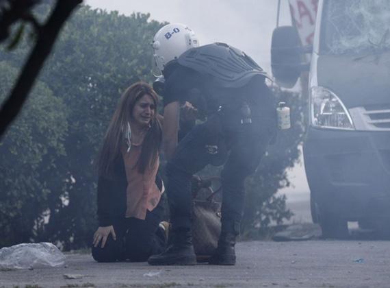 Rémült emberek a tüntetések közepette. A képen éppen egy rendőr segít egy fiatal nőnek.