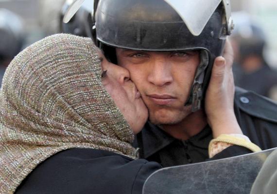 Egy tüntető nő arcon csókol egy rendőrt az egyiptomi kormányellenes felkelések egyikén.