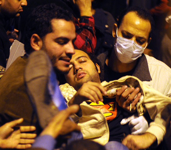 Egy sérült tüntetőnek segítenek Kairóban, a Tahrír téren az összecsapások harmadik napján, hétfőn.