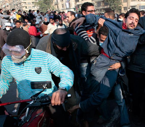 Egy sérültet próbálnak elszállítani motorral a Tahrír térről az összecsapások negyedik napján, kedden.