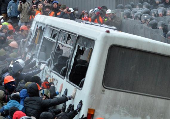 A demonstrálók egy korábban általuk kiégetett rendőrségi buszt próbálnak felborítani.