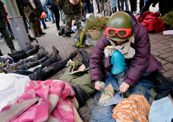 Egy azonosított halott nevét írja a lábára egy kormányellenes tüntető.