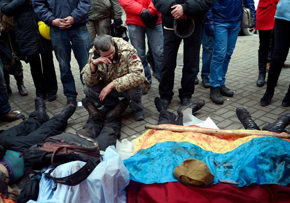 Újabb holttestek: az összecsapások közben elesett társaikat véres ukrán zászlóval takarják le a kormányellenes tüntetők.