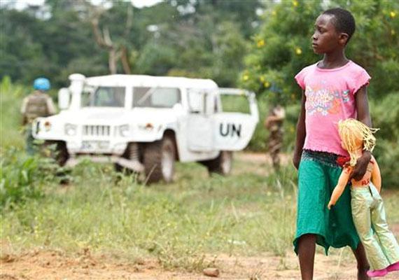 Côte d'Ivoire, 2011: egy kislány sétál a babájával a békefenntartók autója mellett.