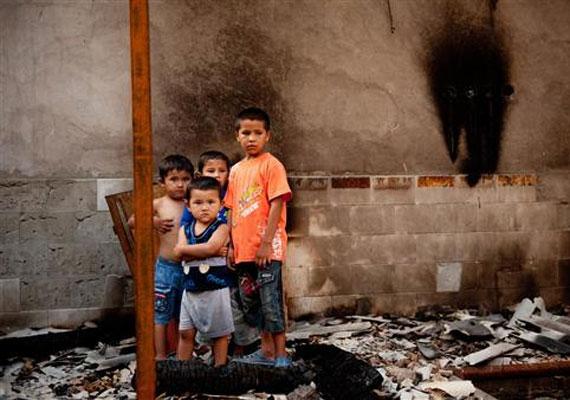 Kirgizisztán, 2010: fiúk állnak egykori otthonuk romjainál. Júniusban az etnikai harcok alatt legalább 356 ember halt meg, és kétezer házat romboltak le.