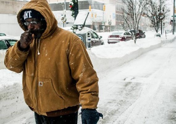 Egy férfi próbálja felmelegíteni a kezét Michigan államban.