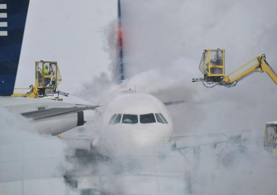 Alkalmazottak próbálják jégteleníteni a befagyott repülőgépet az indianapolisi repülőtéren.