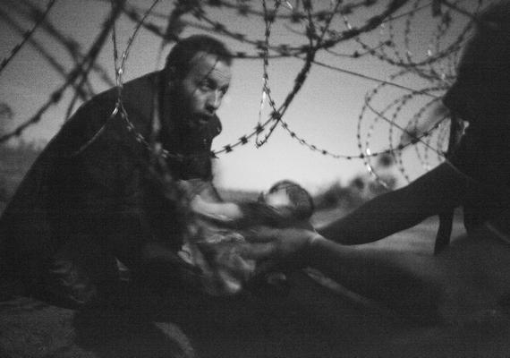 Egy férfi egy kisbabát ad át a kerítés alatt a magyar-szerb határon - Röszke, 2015. augusztus 28., Warren Richardson