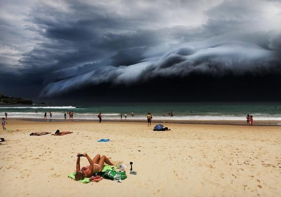 """Egy hatalmas """"felhőcunami"""" tornyosul a Sydney fölé, egy napozó pedig olvas, mit sem törődve a közelgő viharral - Bondi Beach, Ausztrália, 2015. november 6., Rohan Kelly."""