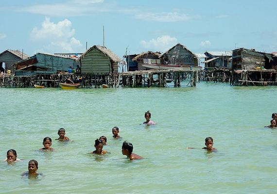 Vízen úszó házak és gyerekek a vízben, egy malajziai bajau faluban. A népcsoport tagjai évszázadok óta hasonló életmódot folytatnak.