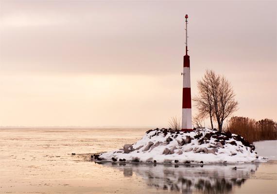 Kis szigetként őrzik a havas kőtömbök a partjelző rudat.