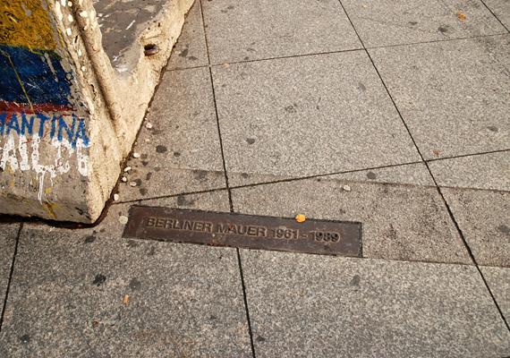 Emlékművek és a földön végighúzódó jelölések őrzik a fal egykori helyét.
