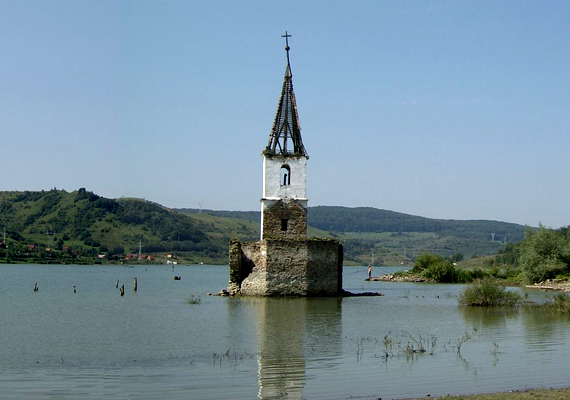 Még látszik a templomtorony. Bár a közeli gát létrehozásának hivatalosan árvízvédelmi szerepe volt - a Küsmöd és a mellékpatakok vizét kellett felfogni nagyobb esőzések után -, a legtöbben a szervezett romániai falurombolást látják Bözödújfalu elárasztásának hátterében.