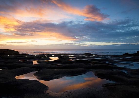 Új-Zélandon, a Muriwai strandon fényképezték, ahogyan az éjszaka kezdi felváltani a nappalt.