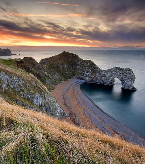 Durdle DoorA tengerbe kúszó, de a szárazföldbe kapaszkodó hatalmas mészkőkapu, a végtelen víz, a parti föveny és az aranyló mezők egyedülálló látványt nyújtanak. Érdemes mindezért legalább egyszer ellátogatni az angliai Jura-partra, a mitikus Dorsetbe.