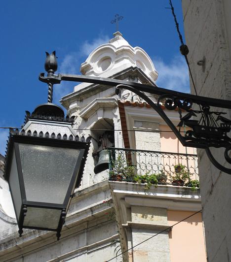 Tipikus utcakép Lisszabonban. Míves lámpa, egy templomtorony és némi növény a balkonon. És természetesen a hihetetlenül tiszta kék ég.