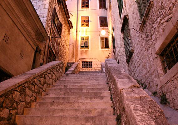 Šibenik - Spoilerveszély!                         A nyaralni vágyók körében népszerű horvát város, Šibenik az ötödik évad forgatási helyszínei között szerepel. A sorozatban Braavos városát jeleníti meg, azt a helyet, ahol a titokzatos, arc nélküli emberek élnek, akik többek között Arya Stark történetszálában játszanak komoly szerepet. A történelmi óváros volt a felvételek központja, és a település négy erődje is beleillett a stáb elképzeléseibe - ezek közül a Szent Mihály-erődöt biztosan láttad már.