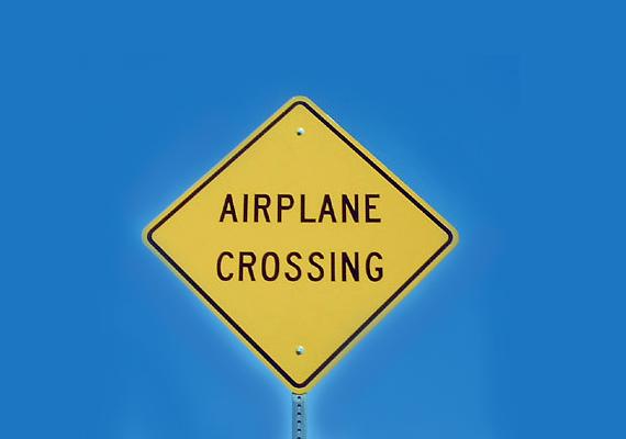 Bár a repülő keresztezi az utat felhívás elsőre viccesnek tűnhet, ilyen létezik, többek között a Gibraltar Airport reptér leszállópályája is egy főutat keresztez.