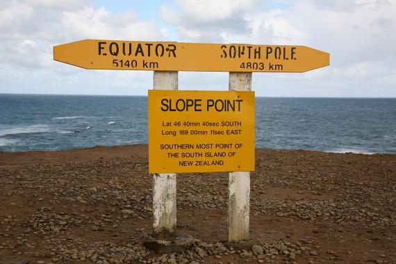 Új-Zéland legdélebbi pontját egy egyszerű sárga tábla jelöli. A Slope Point a világ egyik legszelesebb helye, az áramlat pedig egyenesen az Antarktiszról érkezik. A meredek sziklák kizárólag gyalog közelíthetőek meg, egy birkalegelőről indulva, ahol a környék nevezetességei, a hajlott törzsű fák növekednek.