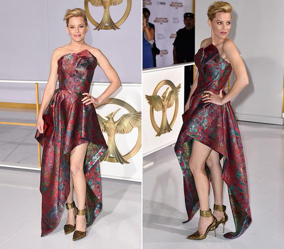 Elizabeth Banks, Effie Trinket megformálója egy hátul hosszú, elöl rövid Leonard ruhakölteményben jelent meg, mely bordó színben pompázott.