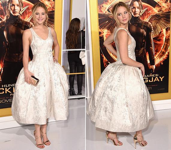 Katniss Everdeen, azaz Jennifer Lawrence egy káprázatosan szép, fehér Dior ruhát választott a bemutatóra, melyet arany szandállal viselt.