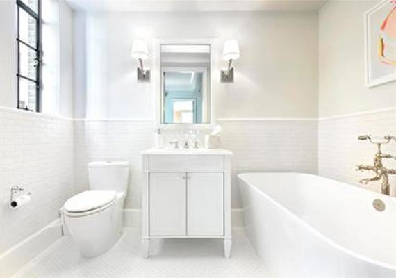 A hófehér bútorokkal berendezett fürdőszoba letisztultságot sugároz.