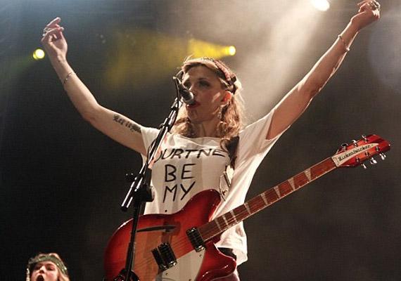 Courtney Love eleinte fehér pólóban, gitárral.