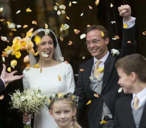 Az ifjú párt sárga rózsaszirmokkal köszöntötték a templomból kilépve.