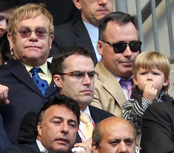 A meleg énekes és fia ugyanolyan morcos fejjel nézi a meccset. Mimikájuk és hajszínük hasonlít, vajon Elton John az apa?