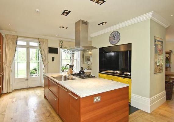 A konyhasziget márványozott munkalappal rendelkezik, a napsárga bútorok vidámságot kölcsönöznek a helyiségnek.