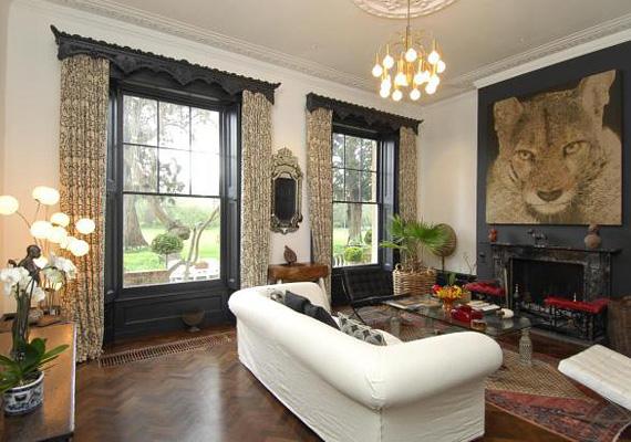 A házban több helyütt is található kandalló, ebben a fogadószobában fehér bútorokkal dobták fel a teret - a letisztultságot sugalló szín a kandalló fölött lévő tigrisre irányítja a figyelmet.
