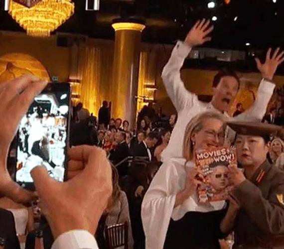 Michael Keaton éppen Meryl Streepet és a morcos észak-koreai katonának öltözött Margaret Cho színésznőt készült fotózni, amikor Benedict Cumberbatch hátulról beugrott a felvételbe. Igaz, ami igaz, így sokkal viccesebb a fotó.