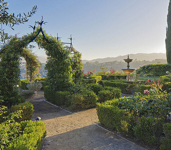 Rózsalugasok és szökőkutak díszítik a kertet, ahol a modell szerint nagyszerűen el lehet bújni, ha éppen az 1100 négyzetméteres ház nem elé.